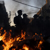 Police officers stand guard next to burning garbage during clashes with ultra-Orthodox Jews in Bnei Brak, Israel, January 24, 2021. (AP Photo/Oded Balilty)