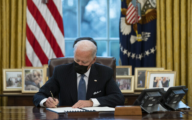 US President Joe Biden signs an executive order in the Oval Office of the White House, in Washington, January 25, 2021. (Evan Vucci/AP)