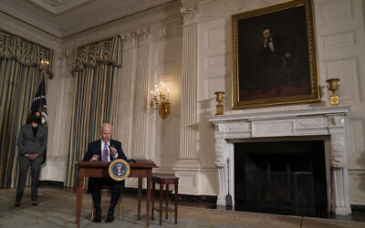 US Vice President Kamala Harris looks on as President Joe Biden signs a series of executive orders in the State Dining Room of the White House, January 26, 2021, in Washington. (AP Photo/Evan Vucci)