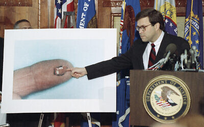 Acting U.S. Attorney General William Barr points to a fragment of a circuit board during a news conference on Pan Am Flight 103 in Washington, Nov. 14, 1991. The tiny fragment was described as part of the bomb inside a portable radio. (AP Photo/Barry Thumma)