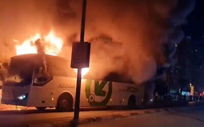 Ultra-Orthodox protesters set a bus on fire during a protest against the enforcement of the coronavirus lockdown, in the city of Bnei Brak, January 24, 2021 (Screencapture/ Twitter)
