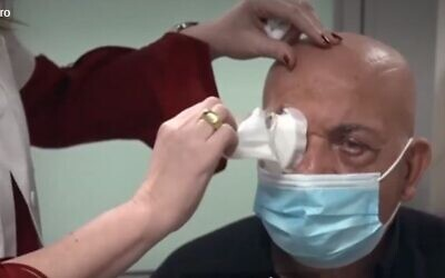 Prof. Irit Bahar, director of the Ophthalmology Department at Rabin Medical Center, removes the bandages from Jamal Furani, after he got the artificial cornea implant developed by CorNeat Vision (Channel 13 screenshot)