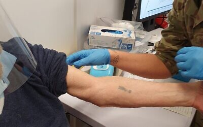 A photo of Auschwitz survivor Herschel Herskovic receiving his COVID shot in the same arm that bears his camp number tattoo taken by his son (Twitter)