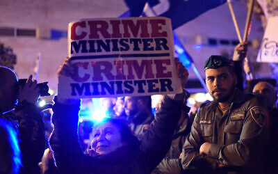 An Israeli woman carries a sign as Left-wing and Right-wing demonstrators are separated by police during protests in support and against Prime Minister Benjamin Netanyahu in Tel Aviv on March 02, 2019. (Gili Yaari/Flash90)