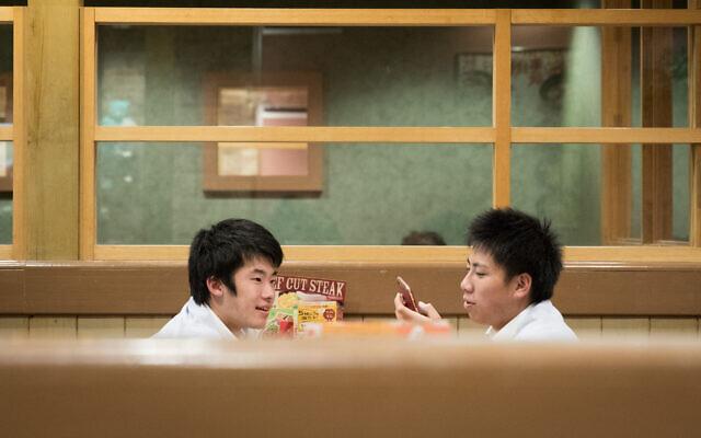Young men at a restaurant in Tokyo, Japan. November 17, 2019. (Nati Shohat/FLASH90)