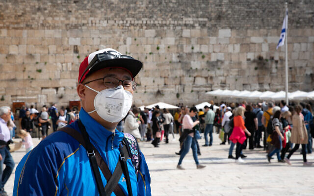 An American tourist wearing a face mask tours at the Western Wall in the Old City of Jerusalem on February 27, 2020 (Olivier Fitoussi/Flash90)