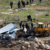 An Israeli bulldozer demolishes a Palestinian farm shed in the West Bank village of Masafer in Area C, in February 2020. (Wisam Hashlamoun/Flash90)