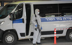 Prison guards wearing protective clothing transport a prisoner suspected of having the coronavirus, at Shaare Zedek Medical Center in Jerusalem, on March 30, 2020. (Yossi Zamir/Flash90)