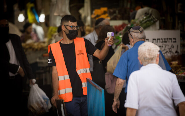 Illustrative: A man checks the temperature of a shopper at the entrance to the Mahane Yehuda Market in Jerusalem on June 18, 2020. (Yonatan Sindel/Flash90)