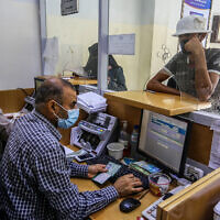 Palestinians receive their financial aid as part of assistance given by Qatar, at a post office in Rafah, in the southern Gaza Strip on October 6, 2020. (Abed Rahim Khatib/Flash90)