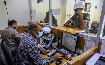 Palestinians receive their financial aid as part of assistance given by Qatar, at a post office in Rafah, in the southern Gaza Strip, on October 6, 2020. (Abed Rahim Khatib/Flash90)