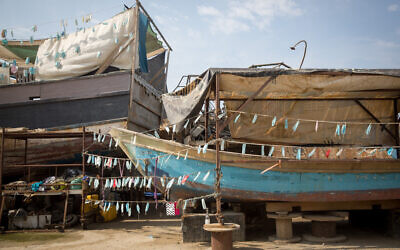 Protective face masks hang on an abandonded boat in the Tel Aviv-Jaffa port on October 28, 2020. (Miriam Alster/Flash90)