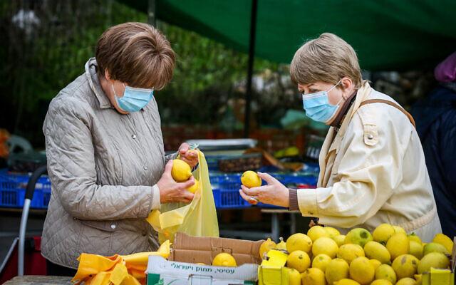 Israeli women inspect lemons at the market in the northern city of Safed on December 9, 2020. (David Cohen/ Flash90)