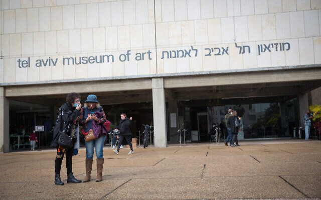 People wear protective face masks due to the coronavirus outbreak as they walk outside the Tel Aviv Museum of Art, December 17, 2020. (Miriam Alster/FLASH90)