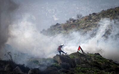 Illustrative: Israeli forces fire tear gas at Palestinians during a clash near  the West Bank city of Nablus on, December 18, 2020. (Nasser Ishtayeh/Flash90)