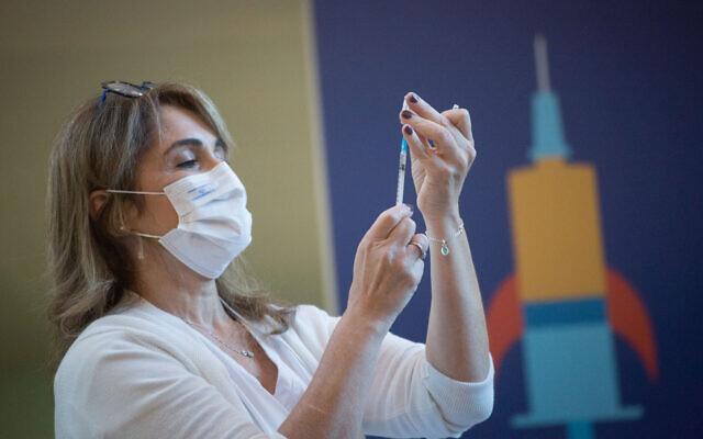 A medical worker prepares a COVID-19 vaccine in Ichilov Hospital in Tel Aviv on December 20, 2020. (Miriam Alster/Flash90)