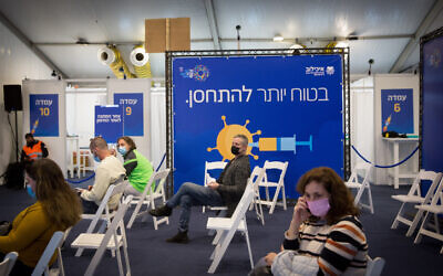 Israelis wait to receive a COVID-19 vaccine at a vaccination center operated by the Tel Aviv Municipality with Tel Aviv Sourasky Medical Center (Ichilov), at Rabin Square in Tel Aviv, December 31, 2020 (Miriam ALster/Flash90)
