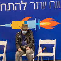 A man waits at a vaccination center in Tel Aviv on December 31, 2020. (Miriam Alster/Flash90)