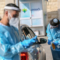 Medical workers test people at a drive-through site to collect samples for coronavirus testing in the northern city of Safed on January 4, 2021 (David Cohen/Flash90)