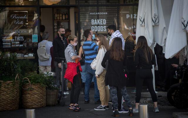 Israelis wait outside a bakery in Tel Aviv