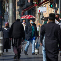 Jerusalemites wear face masks while walking on Jaffa Street on January 6, 2021, during the 3rd lockdown due to the COVID-19 coronavirus pandemic. (Olivier Fitoussi/Flash90)