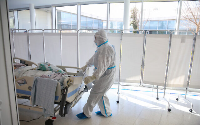 Hospital staff transport a new patient to the coronavirus ward of the Ziv medical center in the northern Israeli city of Safed, January 7, 2020. (David Cohen/Flash90)