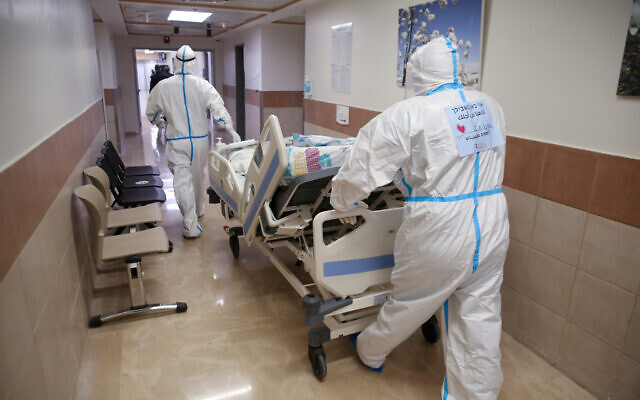 Ziv hospital team members transport a new patient at the coronavirus ward of the hospital  in the northern city of Safed on January 7, 2020. (David Cohen/Flash90)