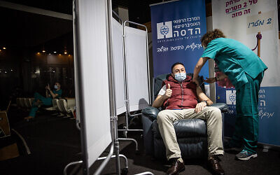 A Hadassah Medical Center staff member receives the second round of the COVID-19 vaccine in Jerusalem, January 11, 2021. (Yonatan Sindel/Flash90)