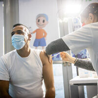 A man receives a coronavirus vaccine injection at Clalit vaccination center in Jerusalem on January 12, 2021. (Yonatan Sindel/Flash90)