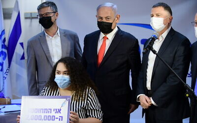 Prime Minister Benjamin Netanyahu (C) and Health Minister Yuli Edelstein (R) at a Maccabi Healthcare Services clinic in the central city of Ramle, as a kindergarten teacher becomes the 2 millionth Israeli to be vaccinated against COVID-19, January 14, 2021. (Tomer Neuberg/Flash90)