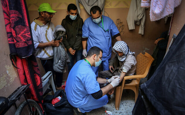 The Palestinian Ministry of Health crews conduct random checks through blood in the town of Rafah, southern Gaza Strip, on January 14, 2021. For the first time, preventive medicine will contact citizens to complete hundreds of checks during blood sampling, to avoid violating the curfew measures. The blood test helps measure anti-bodies. (Abed Rahim Khatib/Flash90)