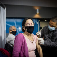 A woman receives a COVID-19 vaccine injection, at a Clalit Health Services vaccination center in Jerusalem, on January 18, 2021. (Yonatan Sindel/Flash90)
