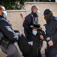 Police carry away an ultra-Orthodox man during clashes in Jerusalem's Sanhedria neighborhood as police raid a yeshiva that violated coronavirus lockdown rules, January 19, 2021. (Yonatan Sindel/Flash90)