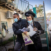 Police officers raid a Yeshiva that is open in violation of the COVID-19 emergency regulations, in the Sanhedria Neighborhood of Jerusalem on January 19, 2021. (Yonatan Sindel/Flash90)