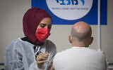 An Israeli man receives a COVID-19 vaccine, at a Maccabi Health Services vaccination center at the Givatayim mall, outside of Tel Aviv, January 20, 2021. (Miriam Alster/Flash90)