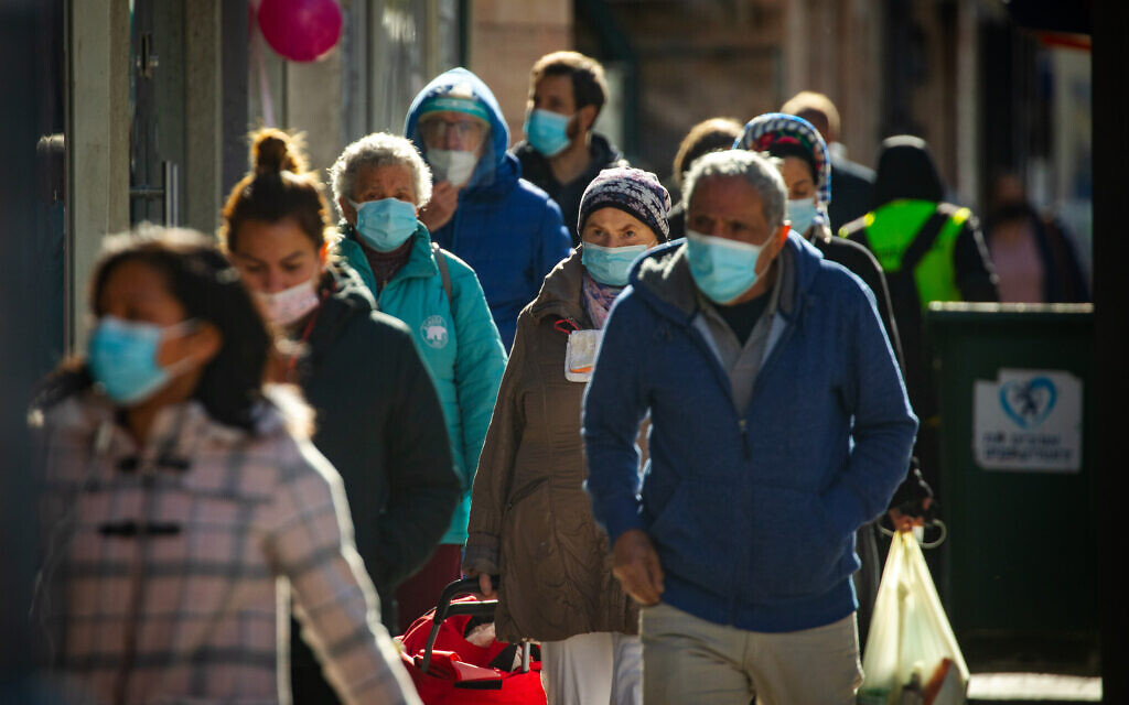 Israelis wearing face masks walk in downtown Jerusalem on January 21,  2021, during the third national coronavirus lockdown. (Olivier Fitoussi/Flash90)