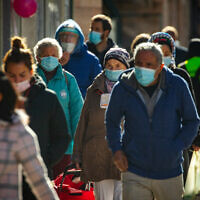 Israelis wearing face masks walk in downtown Jerusalem on January 21,  2021, during the third national coronavirus lockdown. (Olivier Fitoussi/Flash90)