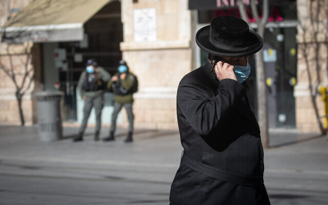 An Israeli man wearing a face mask walks in downtown Jerusalem on January 21, 2021, during a 3rd national coronavirus lockdown. (Olivier Fitoussi/Flash90)
