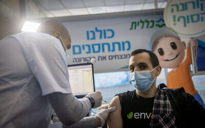 A medical worker administers a COVID-19 vaccine at a Clalit vaccination center in Jerusalem, on January 21, 2021. (Yonatan Sindel/Flash90)