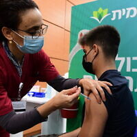An Israeli student receives a COVID-19 vaccination, at a Kupat HolimLeumit center in Tel Aviv, on January 23, 2021. (Avshalom Sassoni/Flash90)