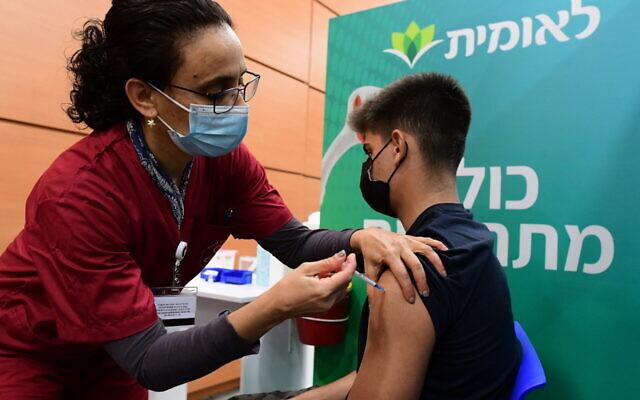 An Israeli student receives a COVID-19 vaccination, at a Kupat HolimLeumit center in Tel Aviv, on January 23, 2021. (Avshalom Sassoni/Flash90)