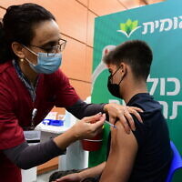 An Israeli student receives a COVID-19 vaccine injection, at a vaccination center in Tel Aviv, on January 23, 2021.  (Avshalom Sassoni/Flash90)