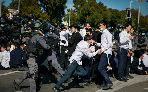 Ultra-Orthodox rioters clash with police after authorities closed a yeshiva that was operating in violation of lockdown orders, in the southern city of Ashdod, January 24, 2021. (Flash90)