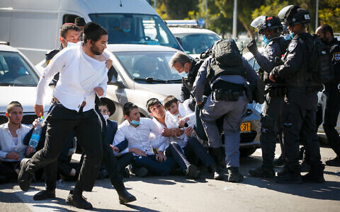 Ultra-orthodox Jews clash with police as they protest after authorities closed a yeshiva that was operating in violation of lockdown orders, in Ashdod, January 24, 2021 (Flash90)
