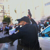 A police officer point his gun in the air during a clash with ultra-Orthodox rioters protesting the enforcement of a lockdown ordered due to the coronavirus, in the city of Bnei Brak, January 24, 2021. (Tomer Neuberg/Flash90)