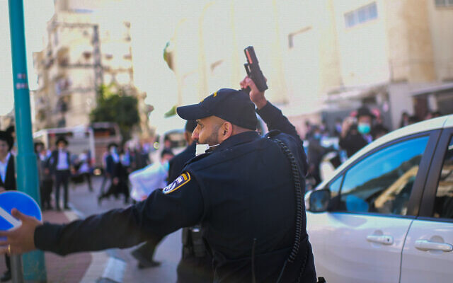 A police officer points his gun in the air during a clash with ultra-Orthodox rioters protesting the enforcement of a lockdown ordered due to the coronavirus, in the city of Bnei Brak, January 24, 2021. (Tomer Neuberg/Flash90)