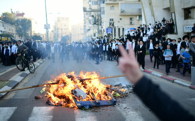 Ultra-Orthodox Israelis clash with police during a protest against the enforcement of the coronavirus lockdown, in the city of Bnei Brak, January 24, 2021 (Tomer Neuberg/Flash90)