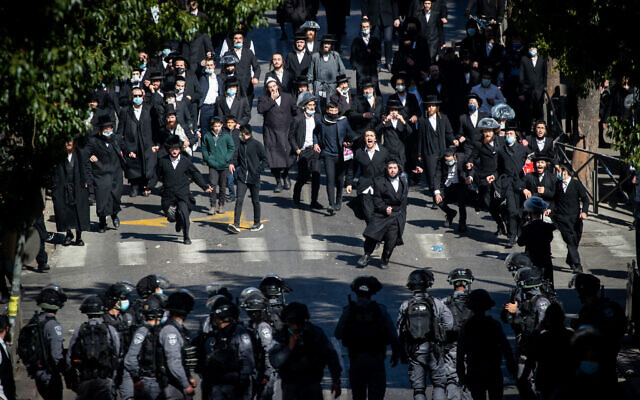 Israeli police clash with Haredi men as they enforce coronavirus restrictions in the Haredi neighborhood of Mea Shearim in Jerusalem, January 24, 2021. (Yonatan Sindel/Flash90)