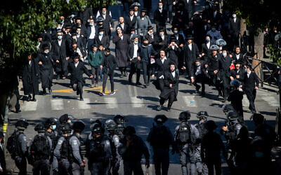 Police clash with Ultra-Orthodox Jewish men during enforcement of coronavirus  regulations, in Mea Shearim, Jerusalem, January 24, 2021 (Yonatan Sindel/Flash90)