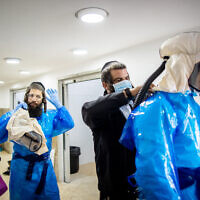Workers from Chevra Kadisha Kehilat Yerushalayim, getting dressed with full protective gear to prepare a body before a funeral at a morgue for people who died from Covid-19, at the Sanhedriya Cemetery in Jerusalem, January 25, 2021. (Yonatan Sindel/Flash90)